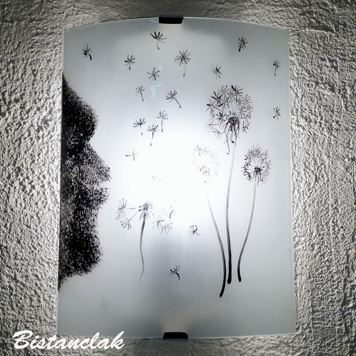 applique murale décorative blanche et noire au dessin d'un souffle sur des pissenlits