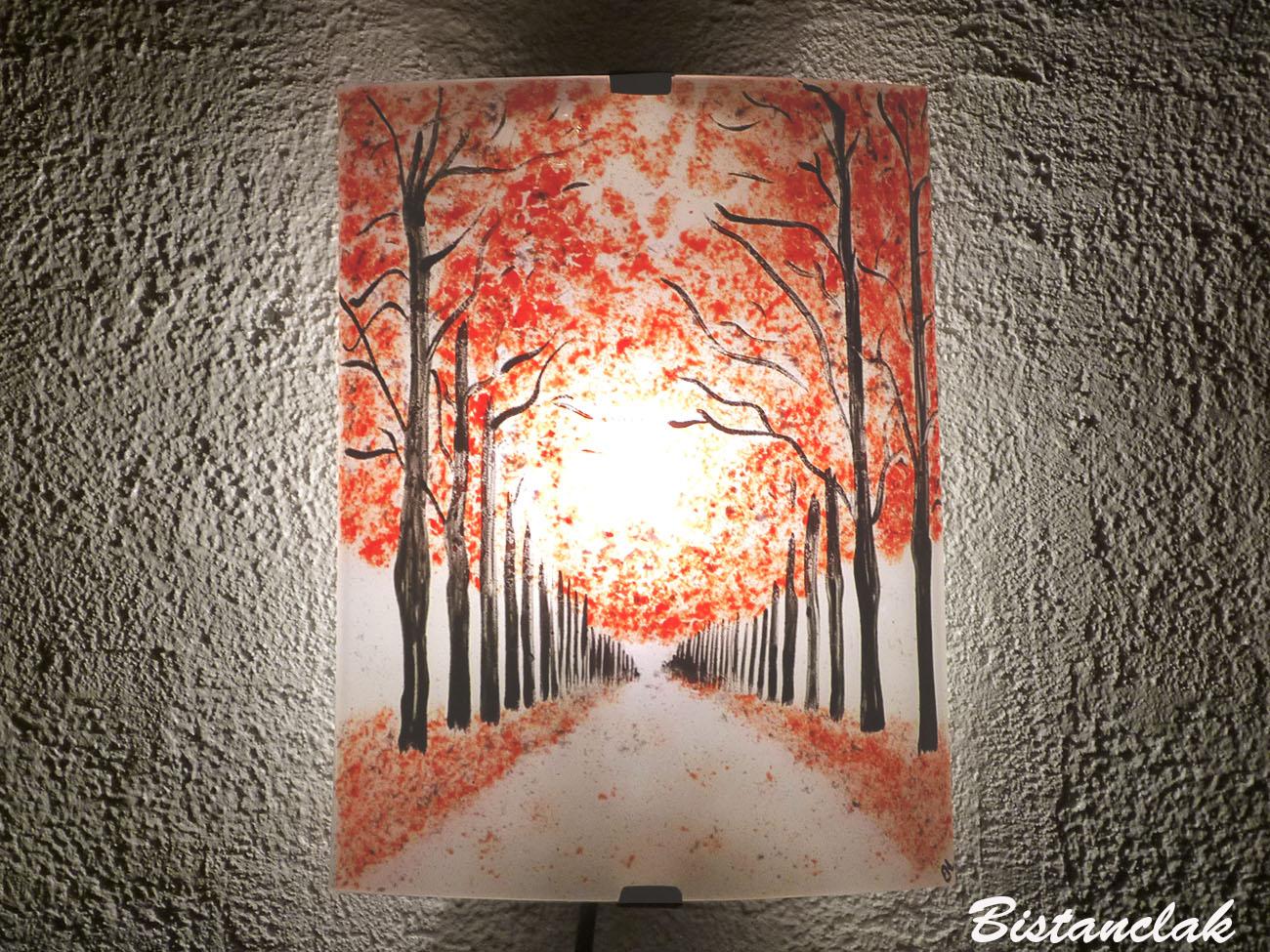 Applique d ambiance en verre au motif d un chemin borde d arbres rouges vendue en ligne sur notre site creation artisanale francaise