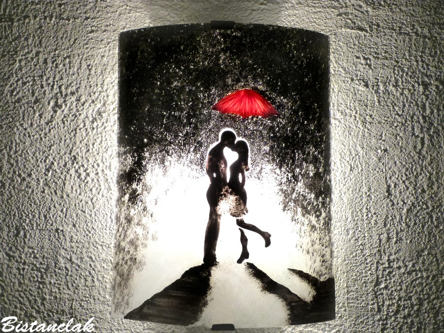 Applique murale demi cylindre artisanal au motif d uun homme et d une femme enlace sous la pluie s echangeant un baiser protege par un parapluie rouge 1