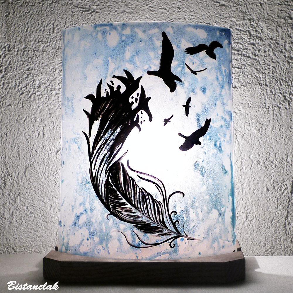 Lampe décorative bleu au motif d'une plume se changeant en oiseaux; création artisanale par Bistanclak, vendue en ligne sur notre site