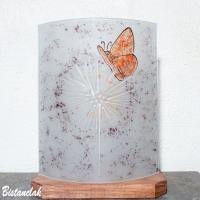 Lampe blanche au dessin d'un papillon rouge sur un pissenlit