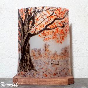 Luminaire artisanal decoratif a placer contre un mur vendu en ligne sur notre site au dessin d un paysage d arbres rouge et mauve et d une balancoire