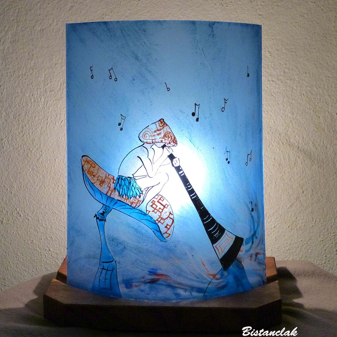 lampe décorative bleu et orange au motif d'un lutin joueur de didjeridoo vendue en ligne