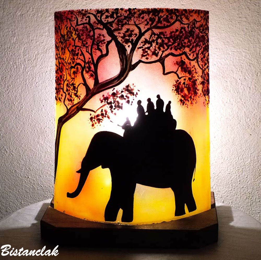 lampe décorative rouge et jaune au dessin d une ballade a dos d elephant